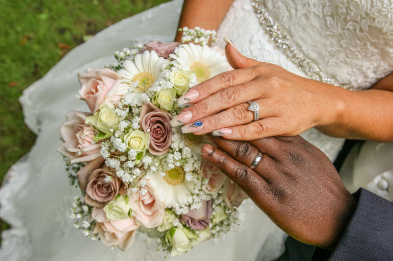 bride and groom hands placed on top of bouquet showing rings on wedding finger